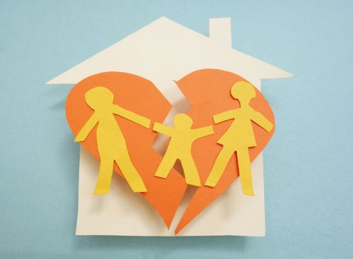 Paper family over torn heart in a house