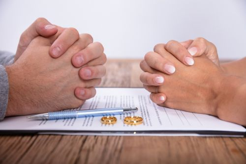 Couple's Hands With Divorce Agreement And Wedding Rings